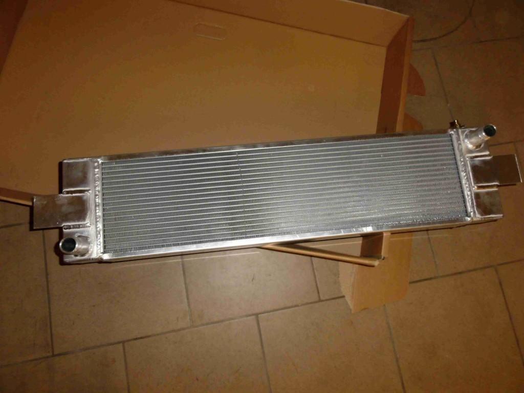 Na obrázku je vyfocen chladiš umístněný na podlaze. Chladič je vyroben z hliníku.